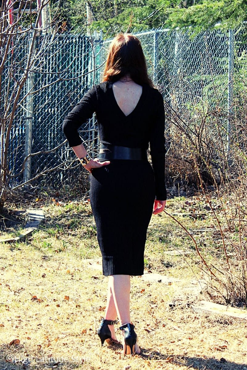 stylist in sexy midi length LBD with back cleavage, belt and heels