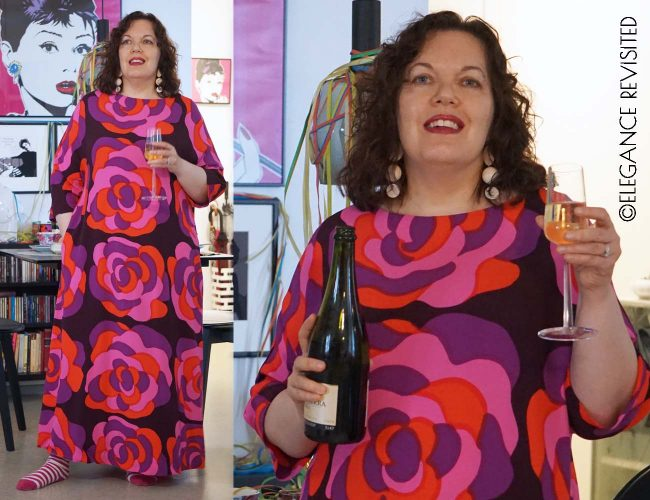 Tiina L in bold orange purple pink and burgundy dress with long earrings