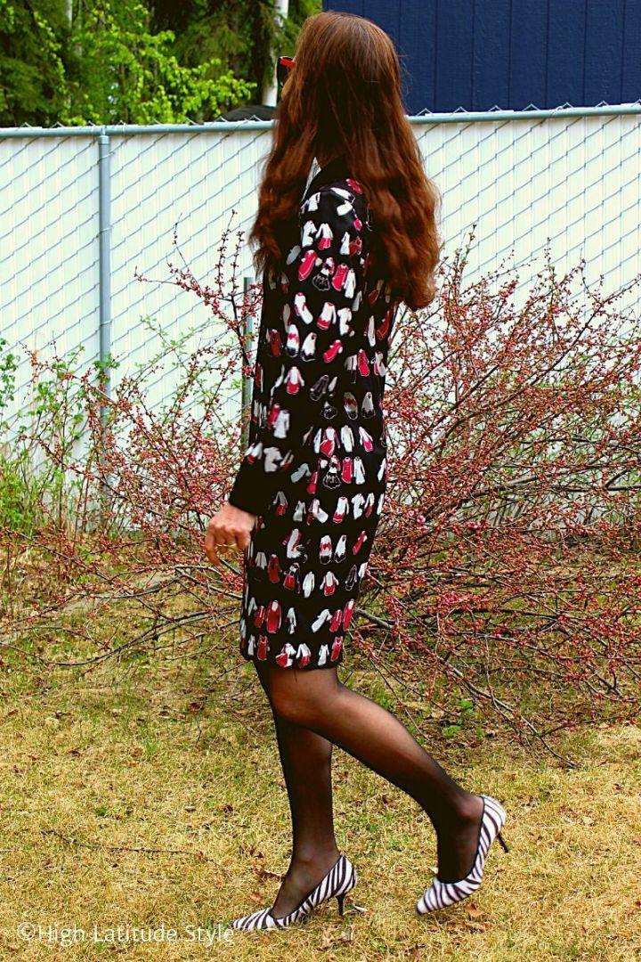 style blogger in zebra print pumps, sheer hosiery, print shift walking on a lawn