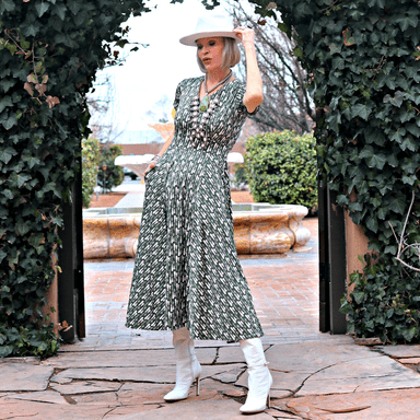 mature woman in romantic pastel print dress with white hat and booties