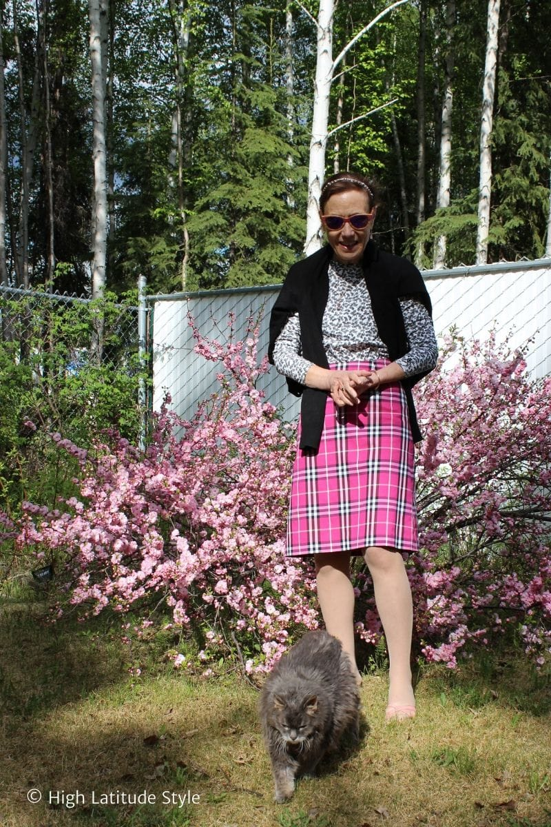Alaskan woman with cat in front of pink bush and birches
