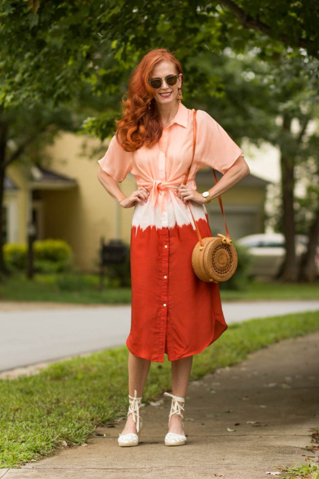 Jess on a sidewalk in tie dye shirtdress in salmon, white and rost