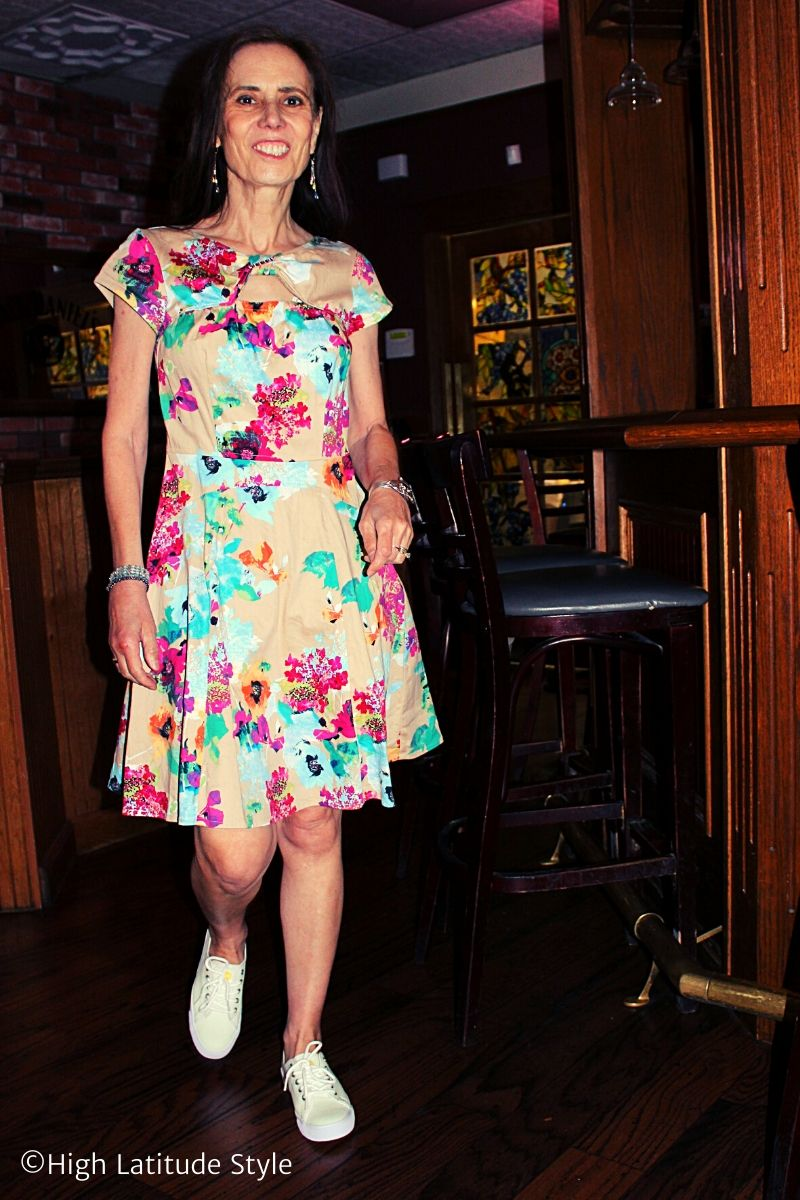 Nicole of High Latitude Style in print dress with color changing Suns Shoes inside a bar