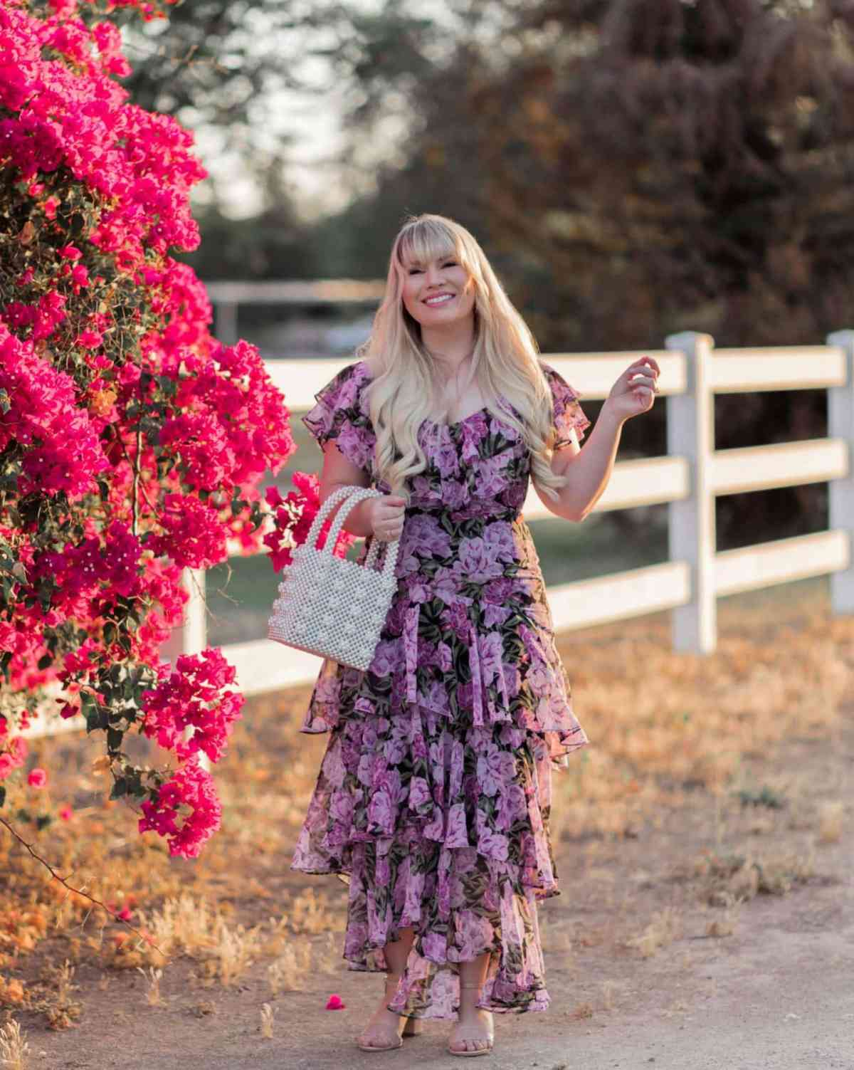 Lizzie in floral chiffon tiered dress on an unpaved road