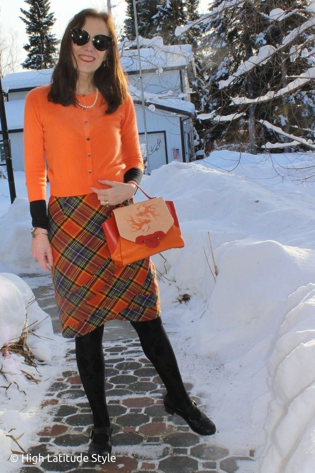 blogger in wrapped plaid skirt, lace tights, Mary-Janes, embellished bag