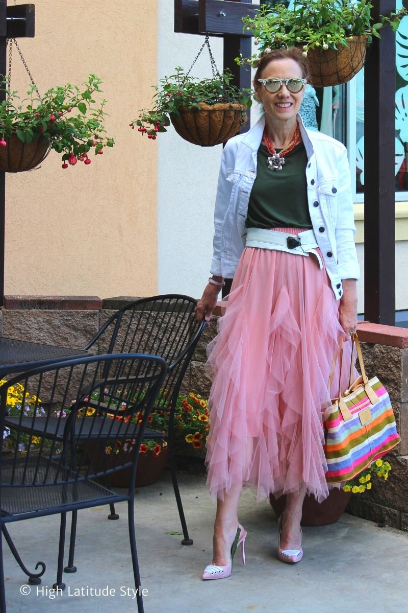 street style blogger in layered rose skirt, white denim jacket, Tee, pumps with striped bag and mirrored wooden sunglasses in a street cafe