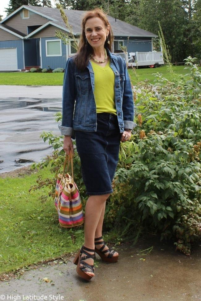 stylist donning a denim straight skirt, yellow sweater, denim jacket and autumn sandals