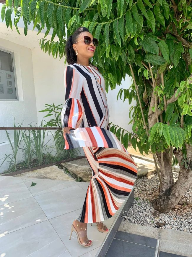 Iris of La Moumous in striped fall dress with pleated sleeves and hem and strappy heels