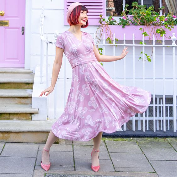woman in pink fit-and-flare dress with white floral print ballet style flats and beret