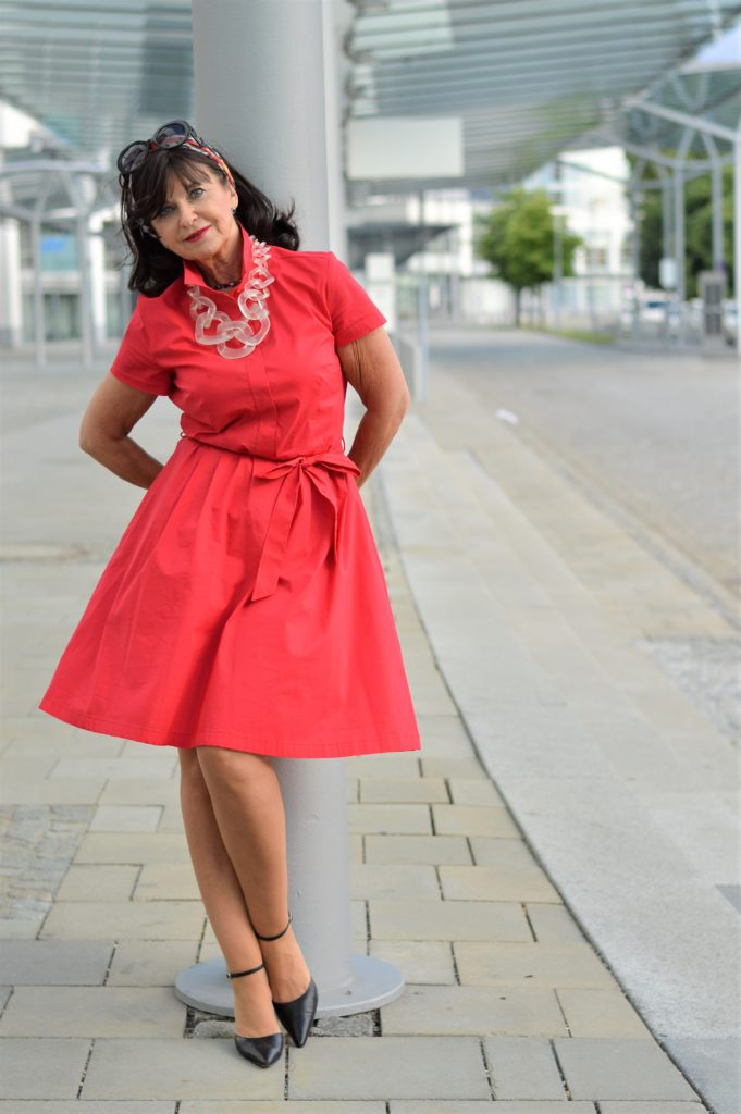 German blogger Martina Berg in a little red dress at a bus station
