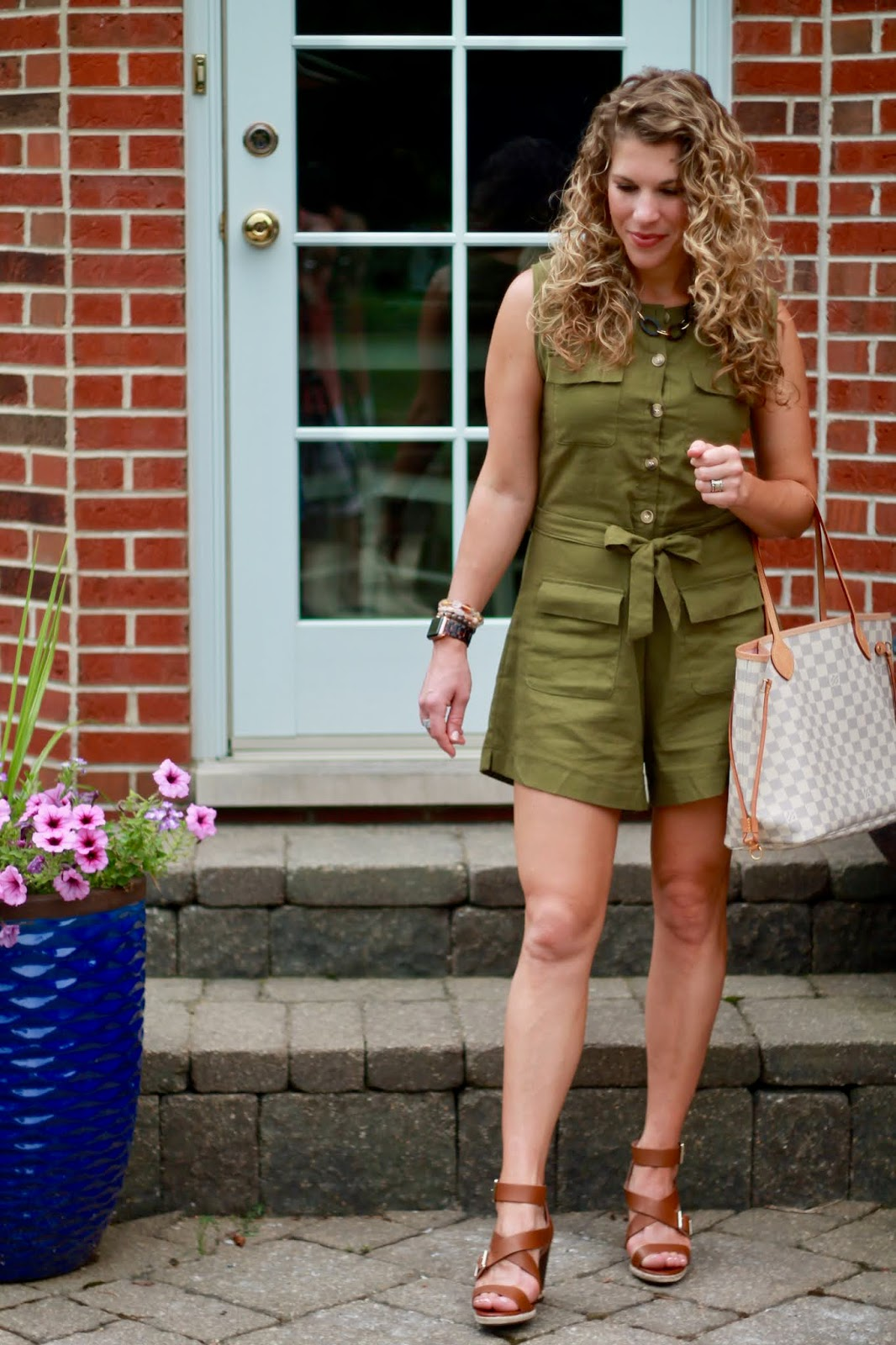 Laura of I Do DeClaire i n olive jumpsuit, brown strappy sandals, statement watch