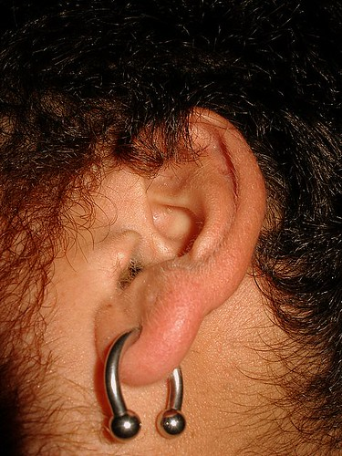 man wearing a modern decoration in his earplugs