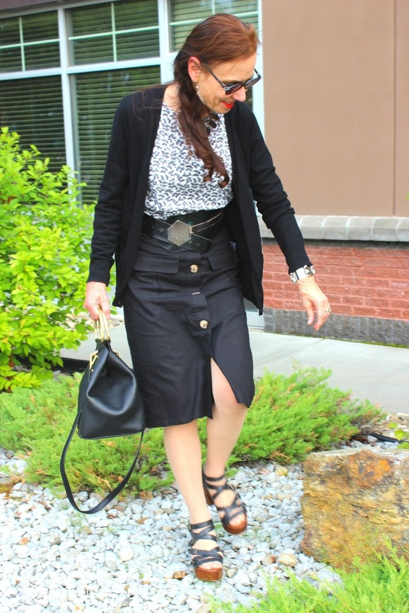 lifestyle blogger Nicole in classic black and white look of skirt, shirt, and cardigan