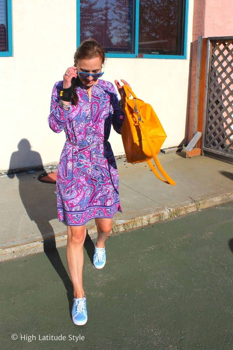 Nicole in trendy paisley dress with marigold bag