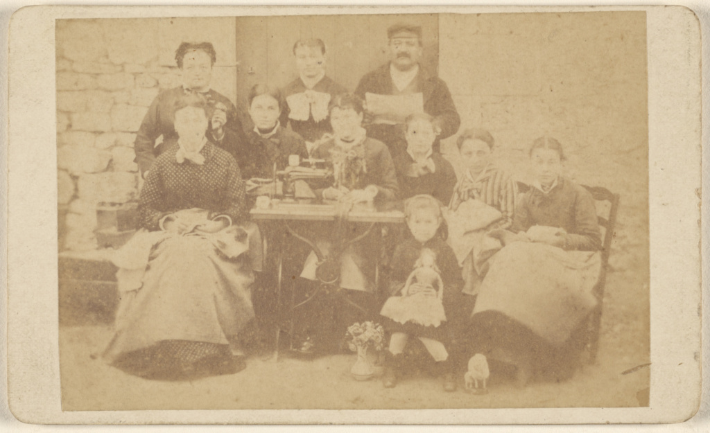 Group of ten men, women, and children sitting around a sewing machine