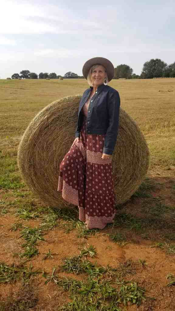 travel blogger Mireille in bohemian brown print dress and denim jacket standing in a harvested field