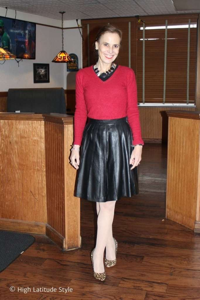 fashion influencer in pleated leather skirt, redsweater, fishnets, statement necklace, leopard pumps