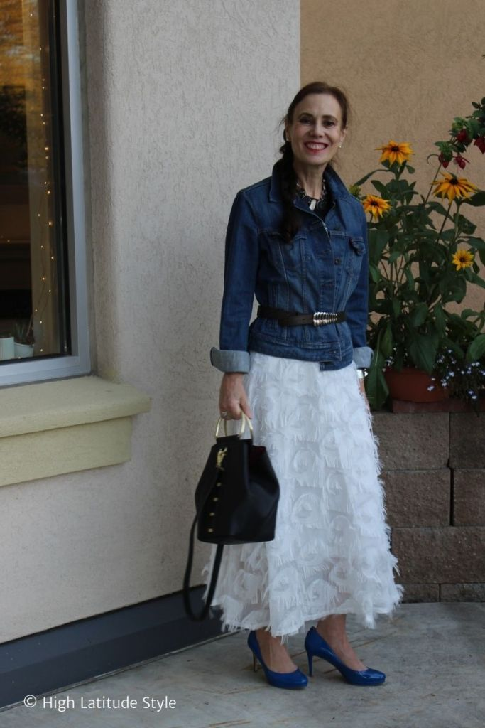 fashion blogger in tea-length A-line skirt embelished with white feathers styled with graphic Tee