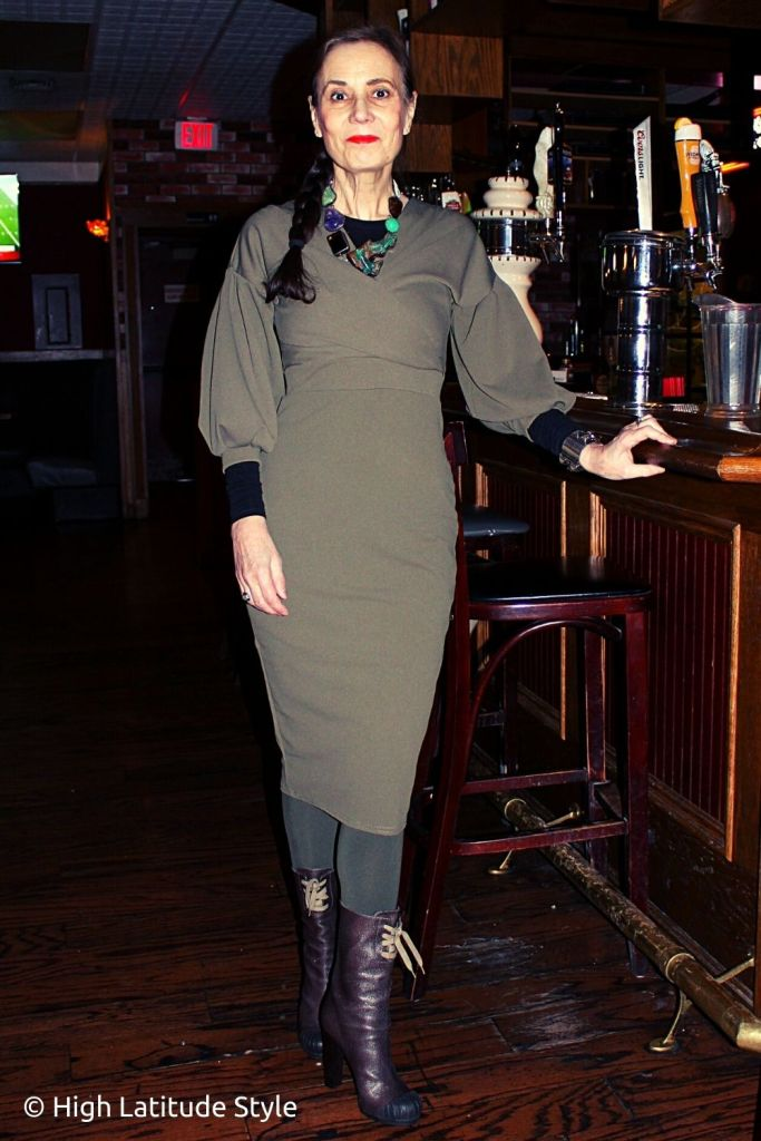 stylist in khaki garment, layering top, tights, booties and statement necklace