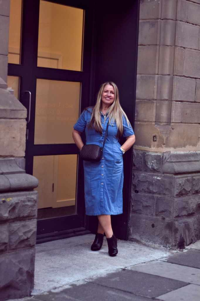 Alison of Midlife and Beyond in denim dress with booties