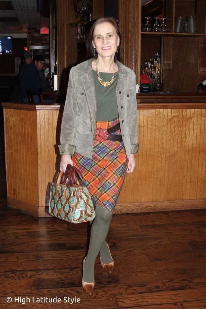 over 50 years old blogger in ornage plaid skirt, olive suede jacket, top and tights winter work outfit