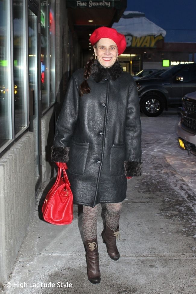fashion influencer in shearling coat, booties, leopard print ights, red gloves, bag and headgear