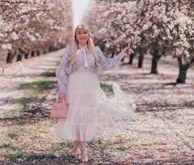 Lizzie in Lace in Easter outfit with tiered white skirt floral top, lilac jacket