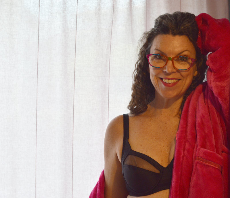 Suzy Turner of the Grey Brunette in bra and red lounge gown