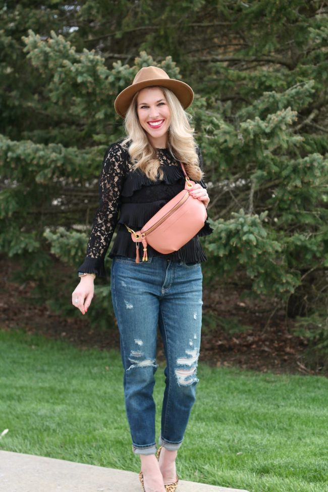 Laura from I do DeClaire in distressed jeans, black sweater, brown hat