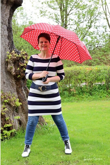 Sabine Grimm in striped dress over skinnies holding a red dotted umbrella