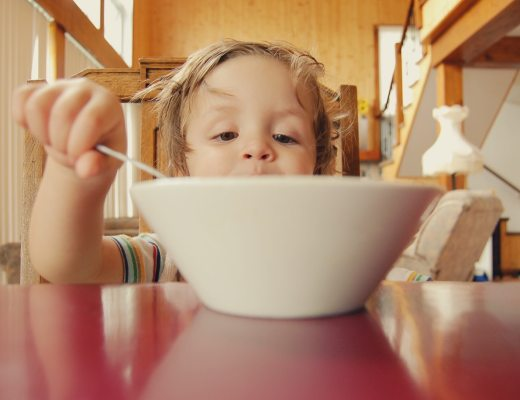 A picky eater child with a bowl of cereal who may be a highly sensitive person