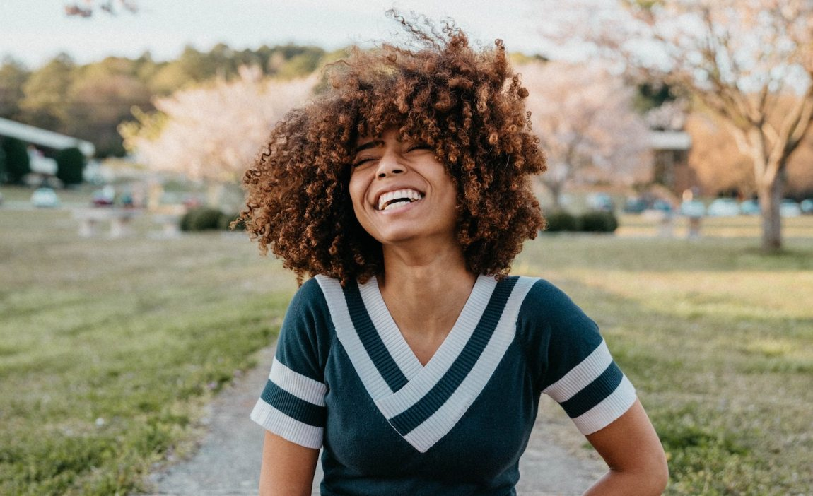 A highly sensitive person (woman) who is an extrovert, smiling and laughing in a park.