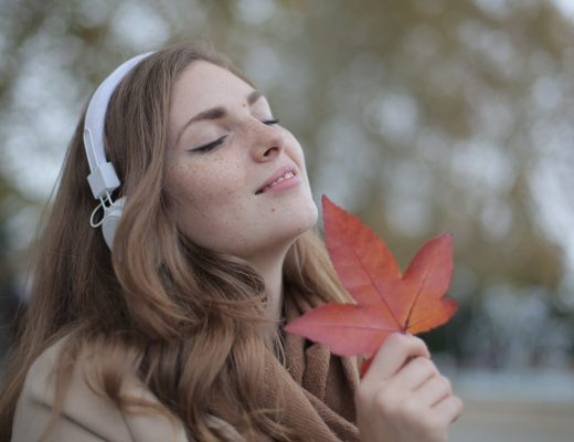 A sensitive person (woman) beaming with a big happy smile and holding an autumn leaf to her face.