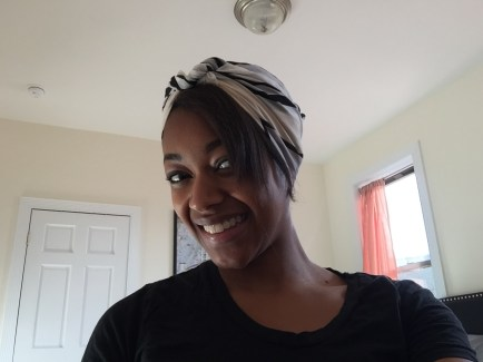 Square, tan headscarf tied in a double knot with the ends tucked in.