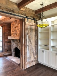 Reclaimed wood sliding doors, mantle, and beams by High Mountain Millwork Company - Franklin, NC
