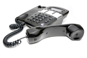 Modern black business office telephone with the receiver off the hook isolated on a white background