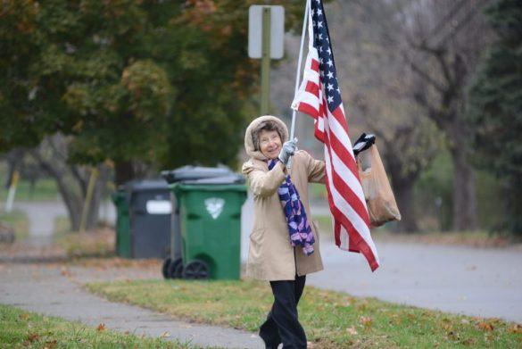 Marilyn Reinking carries U.S. flag through Loveland to raise drug overdose problem awareness.