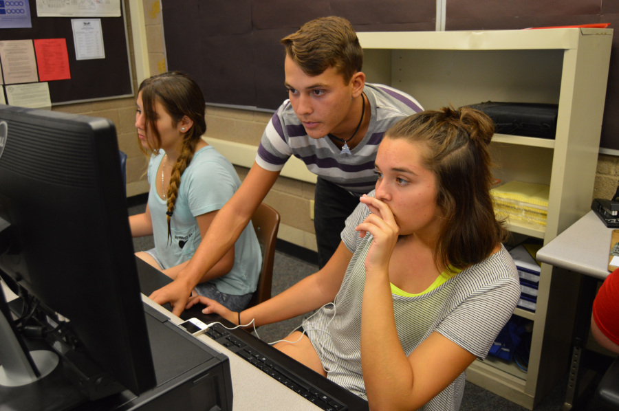 Reef Havel, senior, helps Jillian Coovert, sophomore,  with an assignment in the new Exploring Computer Science class.