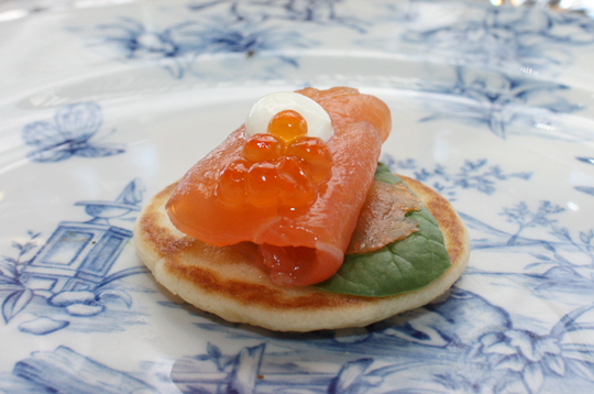 Smoked salmon on blinis with sour cream and salmon pearls