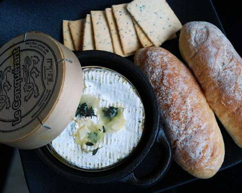 Baked Normandy Camembert with garlic and thyme, served with mini baguettes and lavosh crackers