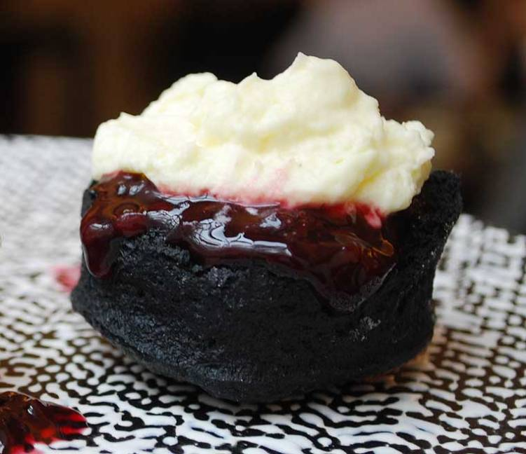 Freshly baked charcoal scones with cream, strawberry preserve