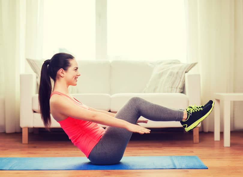 35285520 - fitness, home and diet concept - smiling teenage girl doing exercise on floor at home