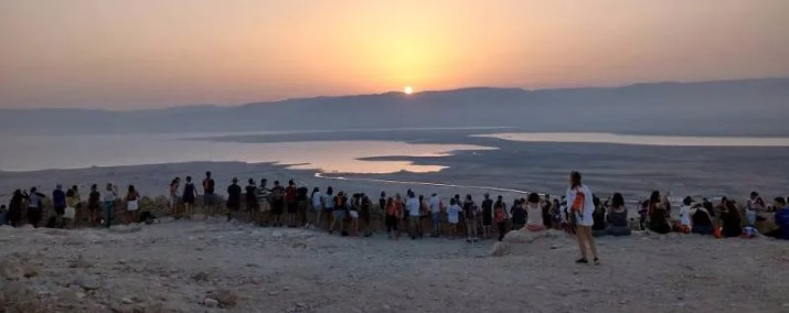 A crowd wathing the sun rise over the dead sea