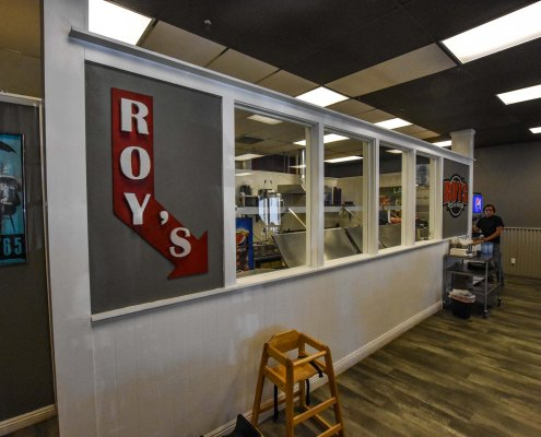 an arrow sign inside Roy's Pizza Restaurant
