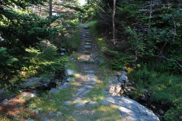 After narrowing from the cart path, the trail descends and crosses a river over a stone bridge.