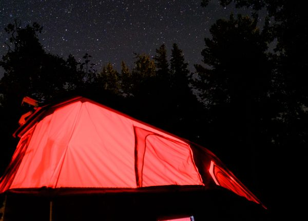 Glow of red light through the Cricket Canvas under the starry sky