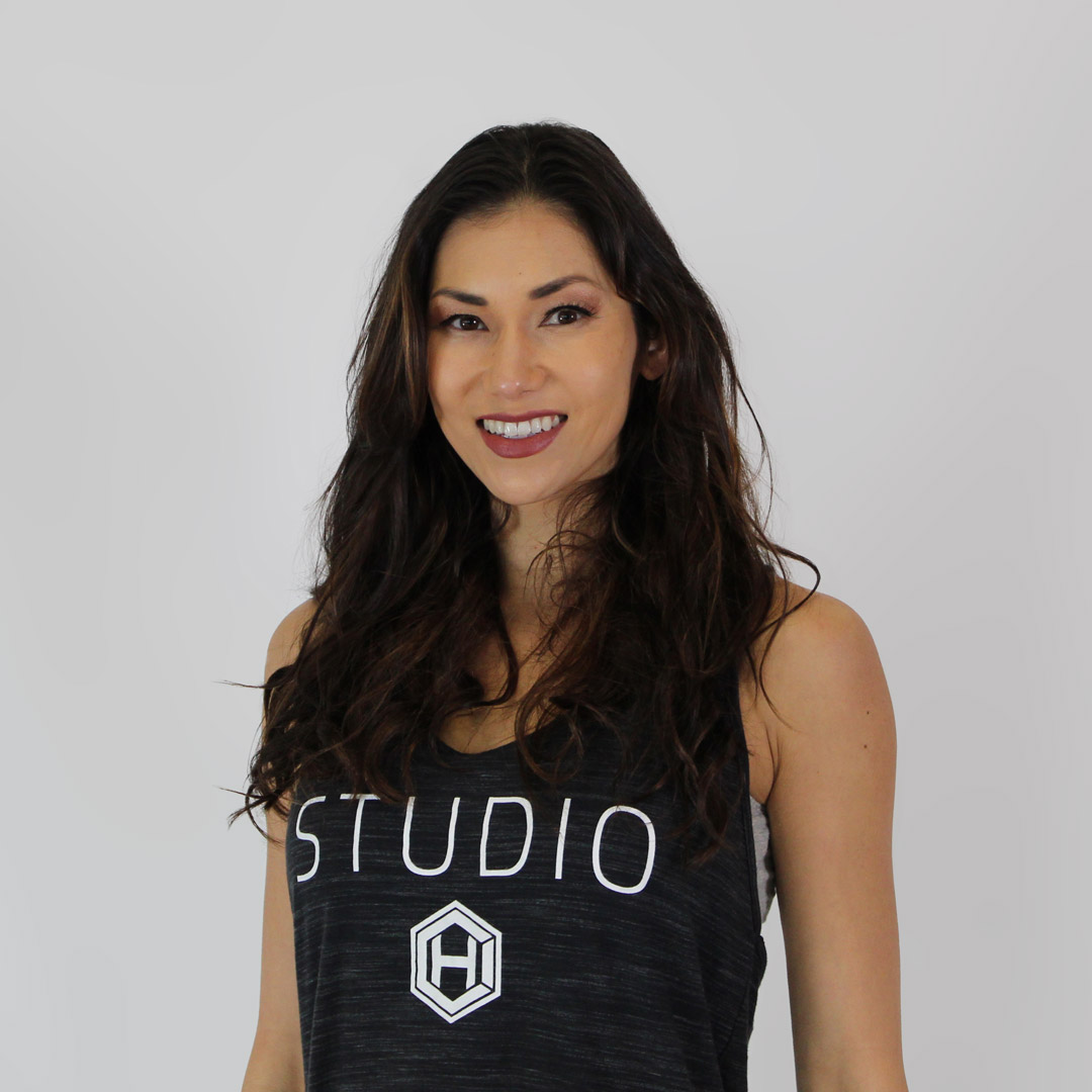 Long, dark-haired woman wearing a black, HCI Studio tank top and smiling