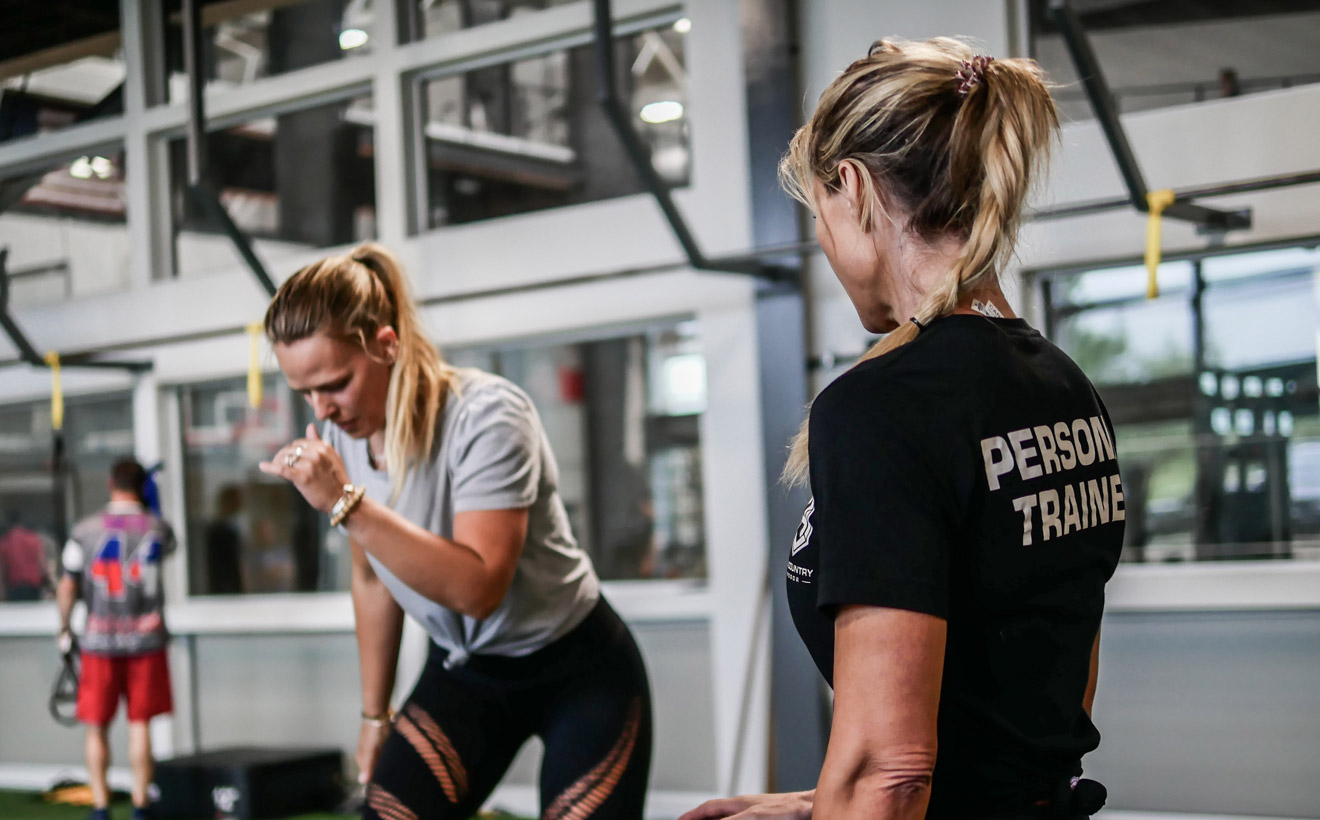 Female, Personal Trainer watching her trainee perform an exercise