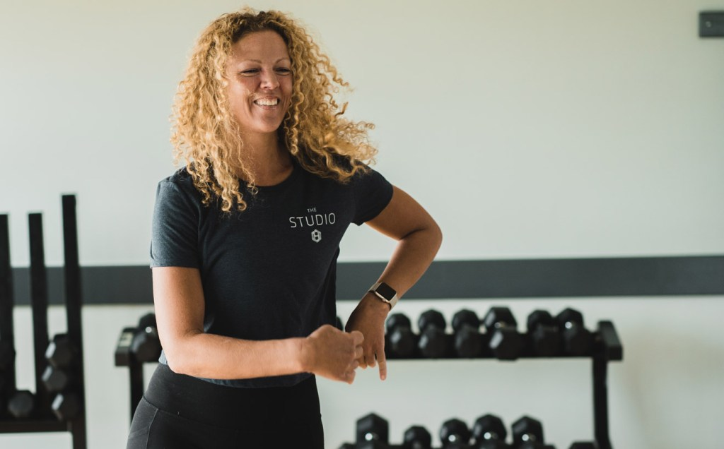 Woman dancing in front of a rack of weights