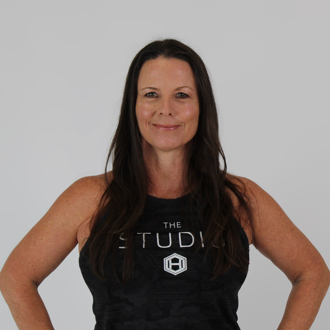 Dark haired woman softly smiling with hands on her hips and wearing a black, hci studio tank top